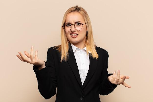 Jeune femme blonde à la perplexité, confuse et stressée, se demandant entre différentes options, se sentant incertaine