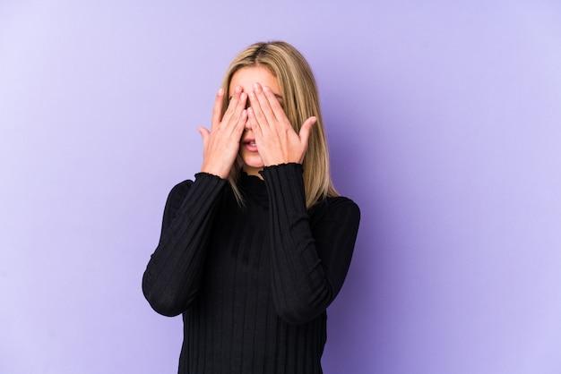 Jeune femme blonde peur couvrant les yeux avec les mains