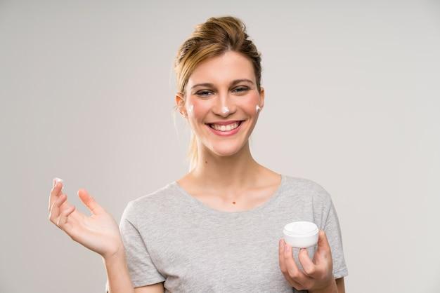 Jeune femme blonde avec un pinceau de maquillage avec une crème hydratante