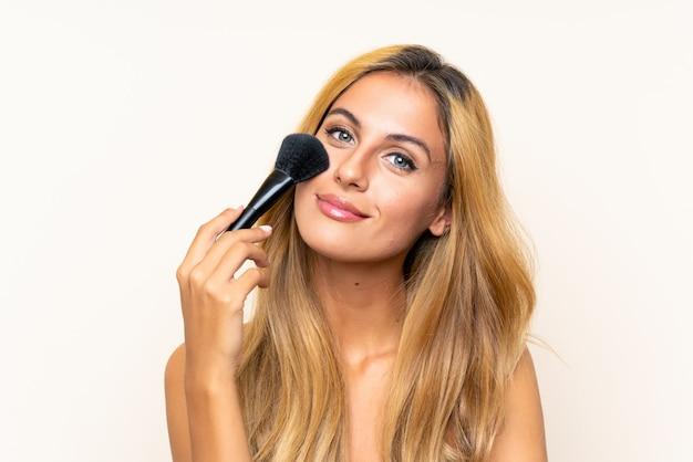 Jeune femme blonde avec un pinceau de maquillage