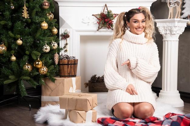 Jeune femme blonde pointant sur des cadeaux près de l'arbre de noël.