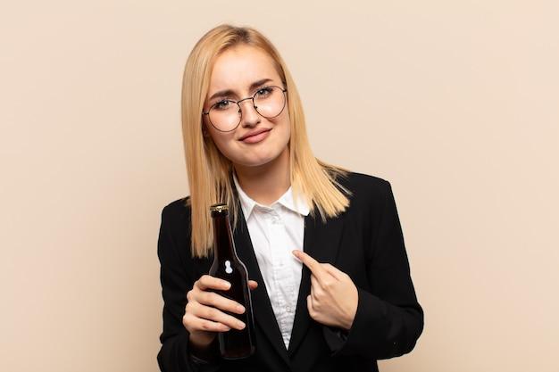 Jeune femme blonde pointant vers elle-même avec un regard confus et interrogateur, choquée et surprise d'être choisie