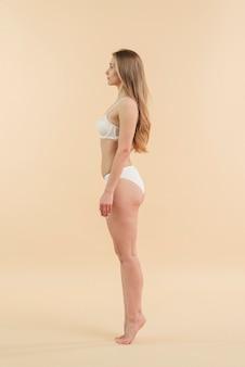 Jeune femme blonde sur la pointe des pieds qui pose en sous-vêtements