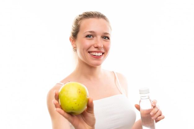 Jeune femme blonde avec une pomme et une bouteille d'eau