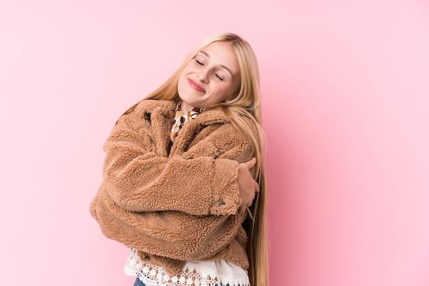 Jeune femme blonde portant un manteau sur un câlin rose, souriant insouciant et heureux.