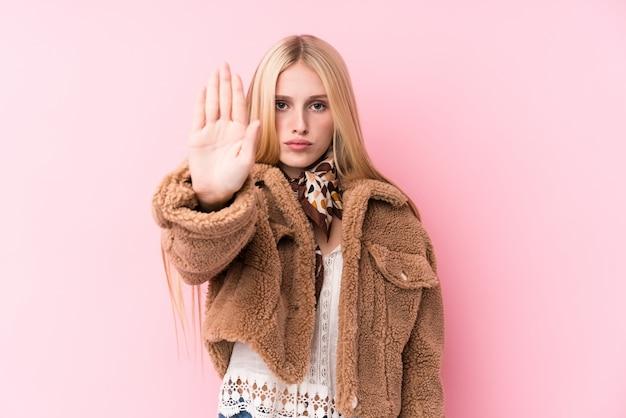 Jeune femme blonde portant un manteau contre un mur rose debout avec la main tendue montrant le panneau d'arrêt