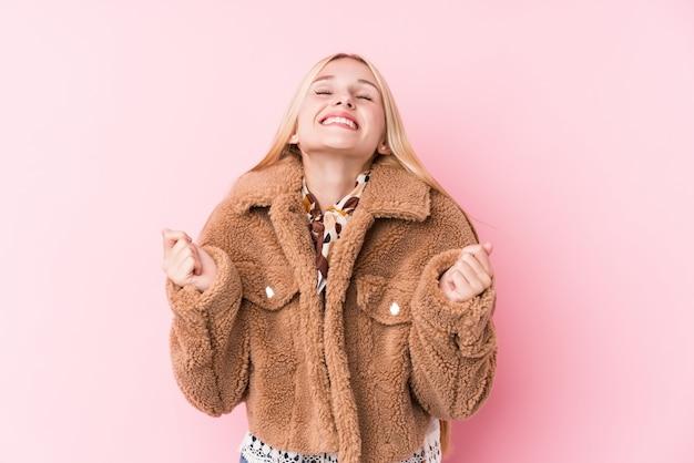 Jeune femme blonde portant un manteau contre un mur rose levant le poing, se sentant heureuse et réussie. concept de victoire.