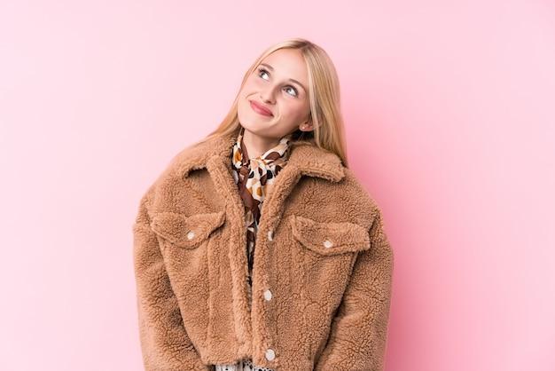 Jeune femme blonde portant un manteau contre un mur rose rêvant d'atteindre des buts et objectifs