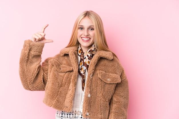 Jeune femme blonde portant un manteau contre un mur rose tenant quelque chose de peu avec l'index, souriant et confiant.