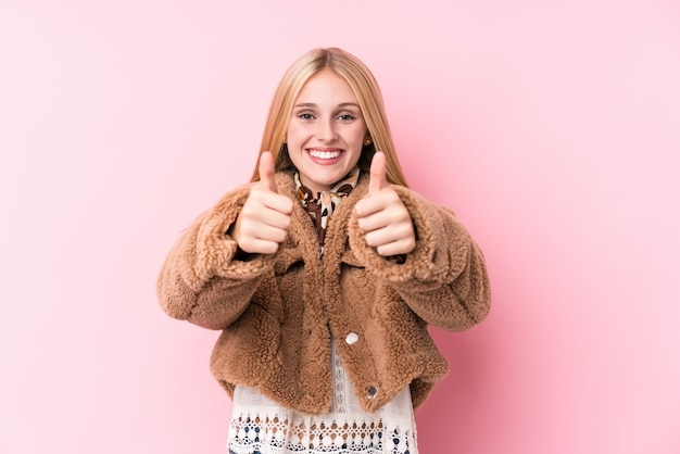Jeune femme blonde portant un manteau sur un fond rose avec le pouce levé, applaudit à quelque chose, soutient et respecte le concept.