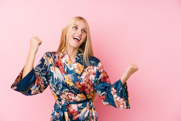Jeune femme blonde portant un pyjama kimono levant le poing après une victoire