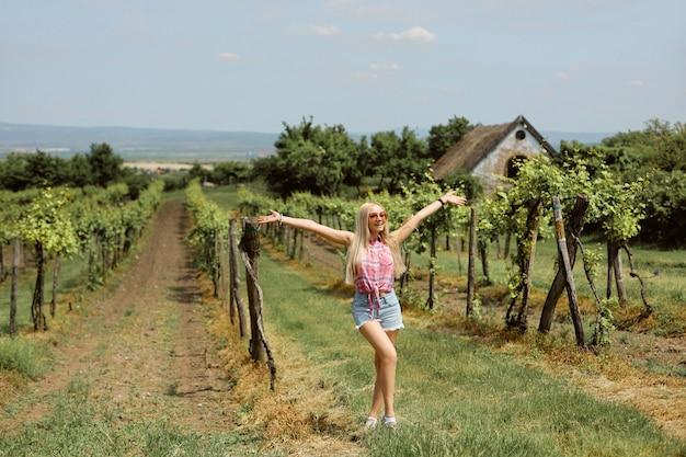 Jeune femme blonde posant dans les vignes pendant la saison estivale. style de campagne d'agriculteur en plein air