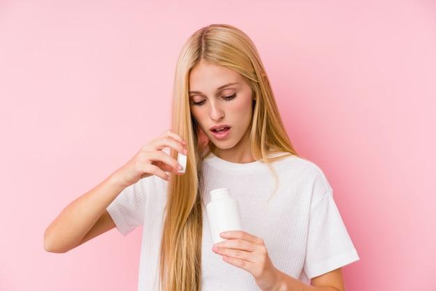 Jeune femme blonde prenant des pilules isolées sur un blackground