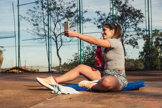 Jeune femme blonde prenant selfie au repos après une séance d'entraînement