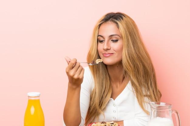 Jeune femme blonde prenant son lait au petit déjeuner