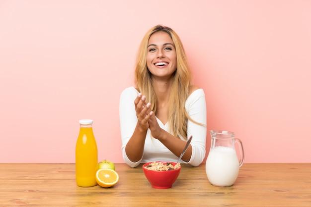 Jeune femme blonde prenant son lait petit déjeuner applaudissant