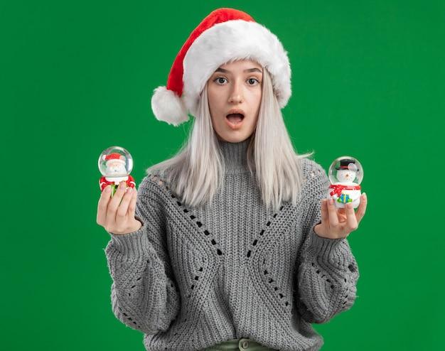 Jeune femme blonde en pull d'hiver et bonnet de noel tenant des boules de neige jouet de noël regardant la caméra étonné debout sur fond vert