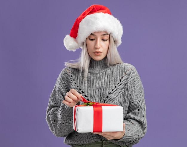 Jeune femme blonde en pull d'hiver et bonnet de noel tenant un cadeau qui va l'ouvrir, intriguée debout sur un mur violet