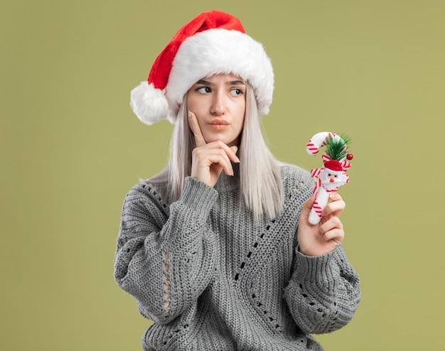 Jeune femme blonde en pull d'hiver et bonnet de noel tenant la canne à sucre de noël à côté perplexe