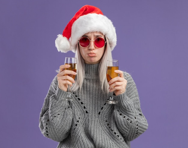 Jeune femme blonde en pull d'hiver et bonnet de noel tenant deux verres de champagne avec une expression triste pinçant les lèvres debout sur un mur violet