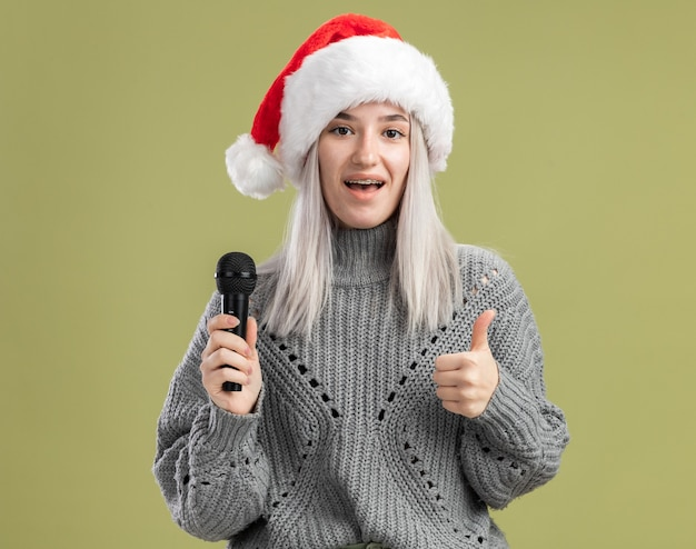 Jeune femme blonde en pull d'hiver et bonnet de noel tenant un microphone avec un sourire sur le visage montrant les pouces vers le haut debout sur un mur vert
