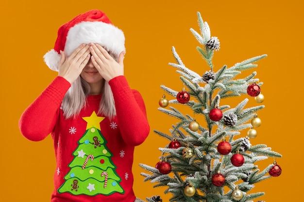 Jeune femme blonde en pull de noël et bonnet de noel couvrant les yeux avec les mains debout à côté d'un arbre de noël sur un mur orange