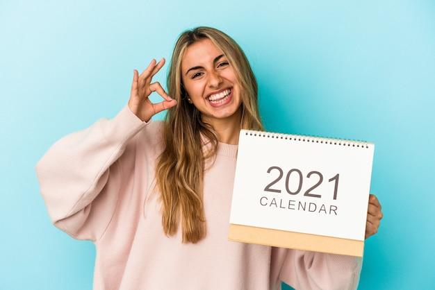 Jeune femme blonde de race blanche trouant un calendrier isolé joyeux et confiant montrant un geste correct.