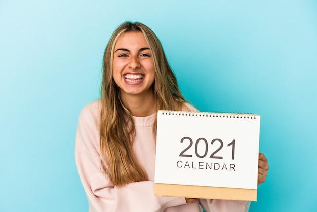 Jeune femme blonde de race blanche trouant un calendrier isolé en riant et en s'amusant.
