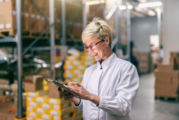 Jeune femme blonde de race blanche en uniforme blanc à l'aide de tablette en entrepôt.