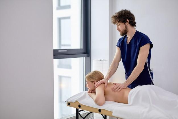 Jeune femme blonde recevant un massage du dos d'un masseur masculin dans un centre de spa