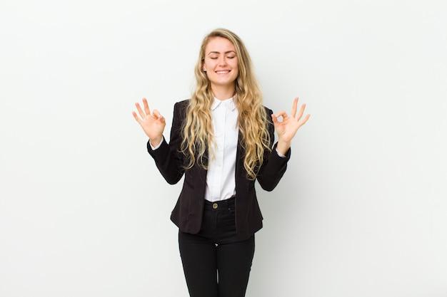 Jeune femme blonde à la recherche concentrée et méditant, se sentant satisfaite et détendue