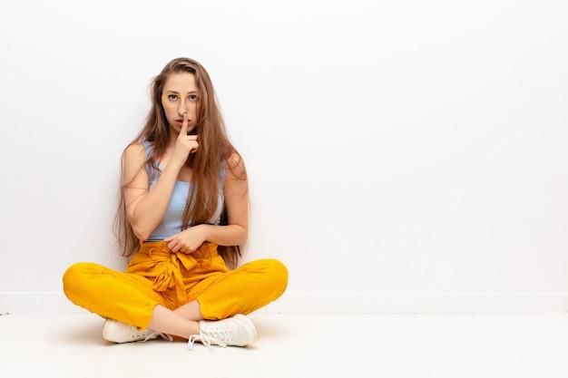 Jeune femme blonde à la recherche sérieuse et croisée avec le doigt appuyé sur les lèvres exigeant le silence ou le calme, gardant un secret assis sur le sol