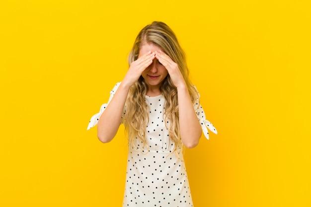 Jeune femme blonde à la recherche de stress et de frustration, travaillant sous pression avec un mal de tête et troublé de problèmes sur le mur jaune