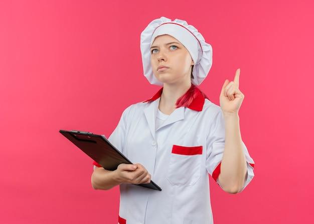Jeune femme blonde réfléchie chef en uniforme de chef tient le presse-papiers et pointe vers le haut isolé sur mur rose