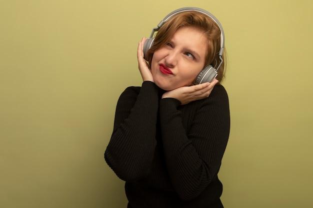 Jeune femme blonde réfléchie portant des écouteurs mettant les mains sur eux en regardant le côté isolé sur un mur vert olive avec espace de copie