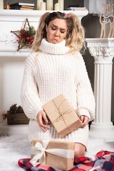 Jeune femme blonde regardant des cadeaux debout près de la cheminée.