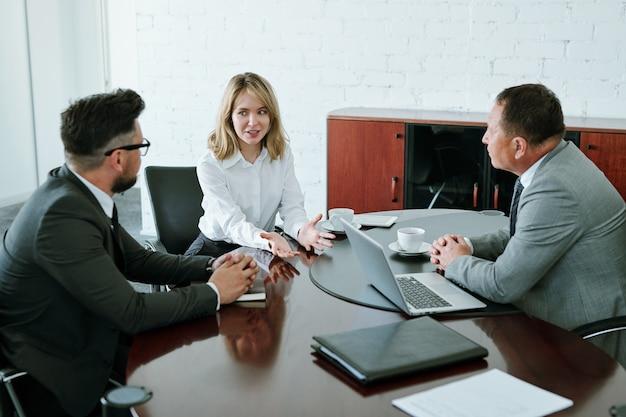 Jeune femme blonde regardant l'un des collègues masculins tout en expliquant son point de vue ou son idée lors d'une réunion de démarrage au bureau