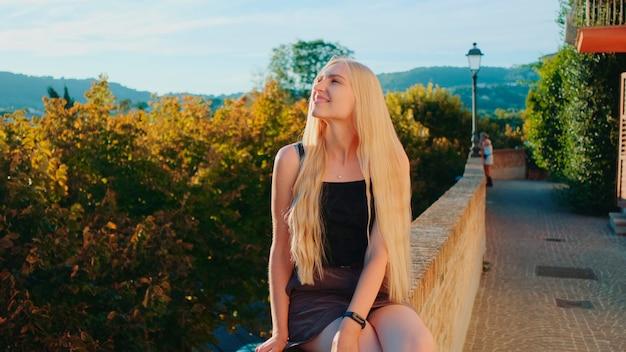 Jeune femme blonde relaxante et souriante dans les rayons du soleil
