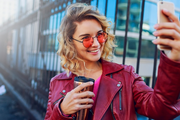 Jeune femme blonde rêveuse marchant dans la ville et utilisant un téléphone intelligent. fermer les détails. fille moderne élégante avec du café. poils venteux.