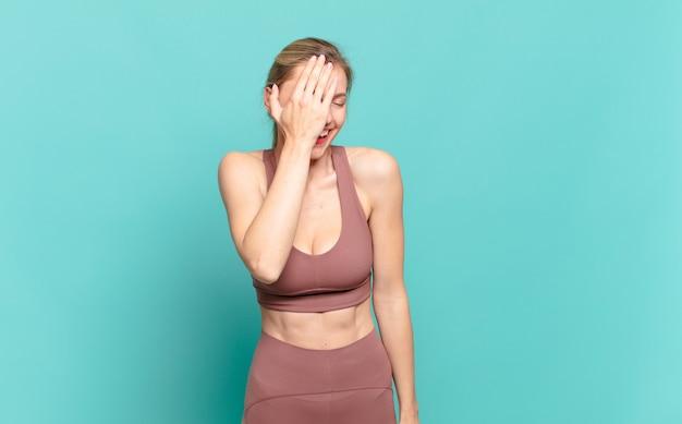Jeune femme blonde en riant et en frappant le front comme pour dire dã¢â€â™oh! j'ai oublié ou c'était une erreur stupide. notion de sport