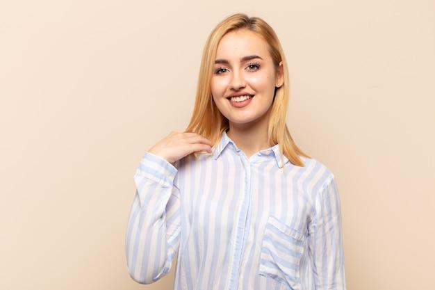 Jeune femme blonde riant joyeusement et en toute confiance avec un sourire décontracté, heureux et amical