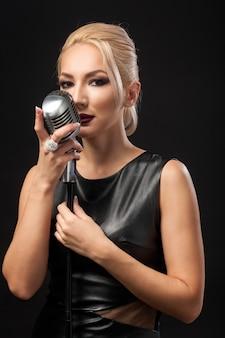 Jeune femme blonde en robe de cuir noir tient un microphone en métal dans les mains