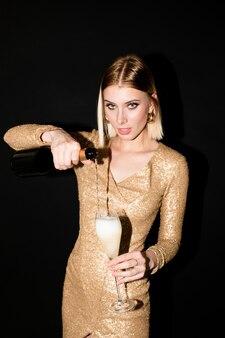 Jeune femme blonde en robe dorée, verser du champagne dans la flûte tout en allant faire des toasts pour l'anniversaire ou une autre occasion à la fête
