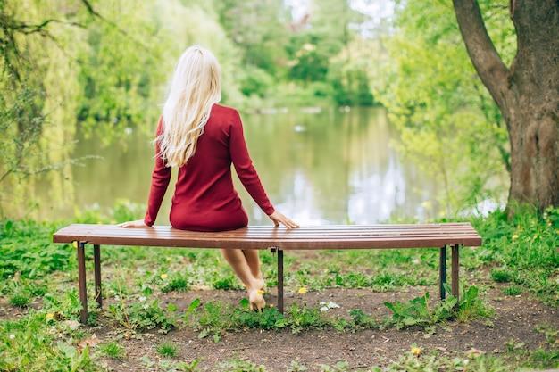 Jeune femme blonde en robe rouge assis sur un banc dans le parc avec vue sur le lac.