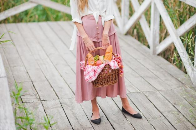 Jeune femme blonde avec une robe vintage de style rétro avec un panier de pique-nique sur une jetée en bois du lac