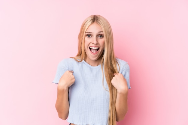 Jeune femme blonde sur rose surprise pointant avec le doigt, souriant largement.