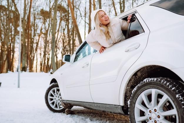 Jeune femme blonde s'asseoir dans sa nouvelle voiture blanche et sourire heureux. assurance, sécurité, location de voiture.