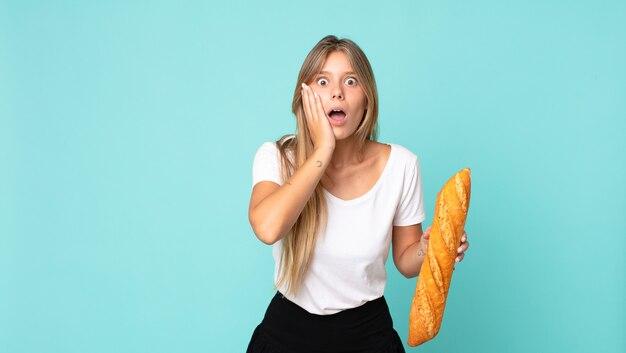 Jeune femme blonde se sentant choquée et effrayée et tenant une baguette de pain
