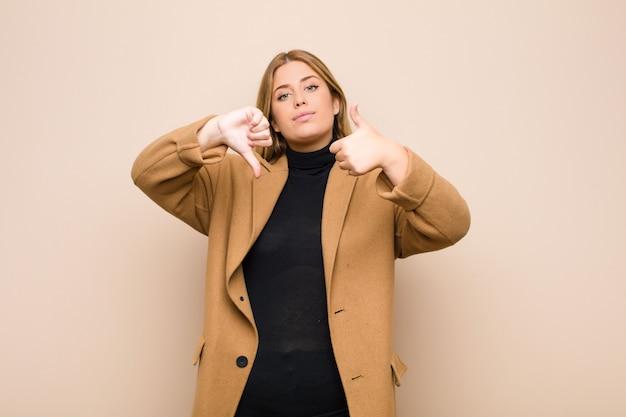 Jeune femme blonde se sentant confuse, désemparée et incertaine, pondérant le bien et le mal dans différentes options ou choix contre un mur plat