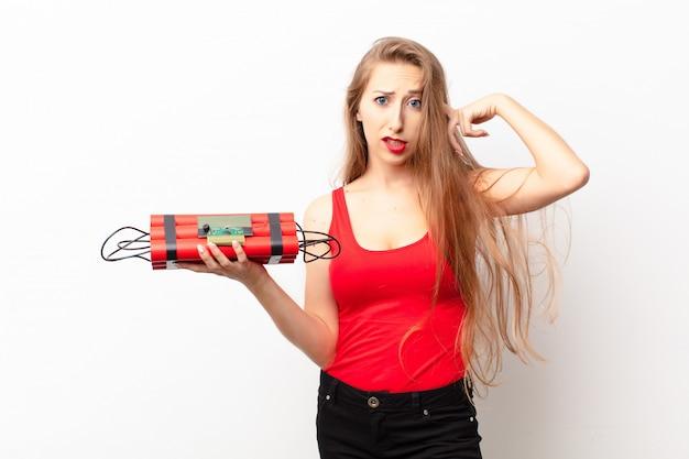 Jeune femme blonde se sentant confuse et perplexe, montrant que vous êtes fou, fou ou fou, tenant une bombe de dynamite